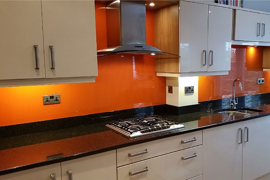 Kitchen with bright orange painted glass splashbacks