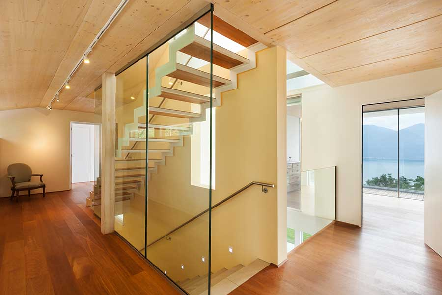 Glass partition walls allow light into this basement staircase