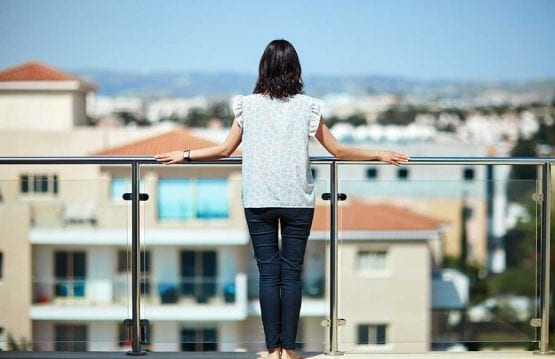 Woman looking at a city view from a glass balcony