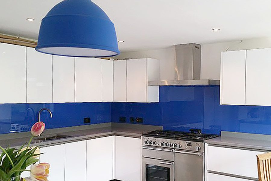 Deep metallic blue glass kitchen splashback