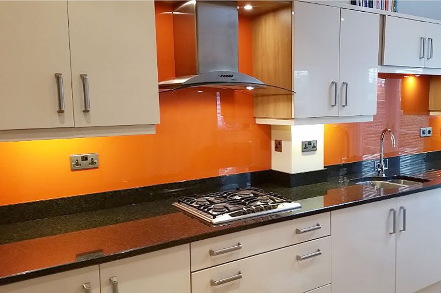 Orange painted glass kitchen splashback