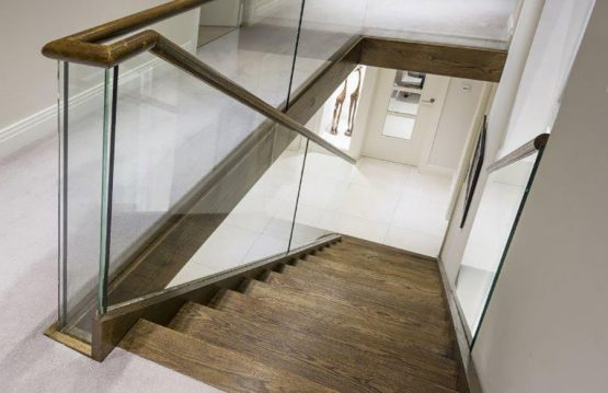 Glass staircase balustrade with dark oak steps