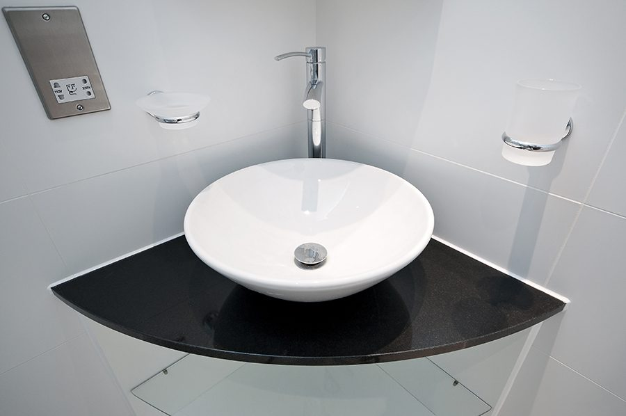 modern bowl style hand wash basin on a granite corner shelf