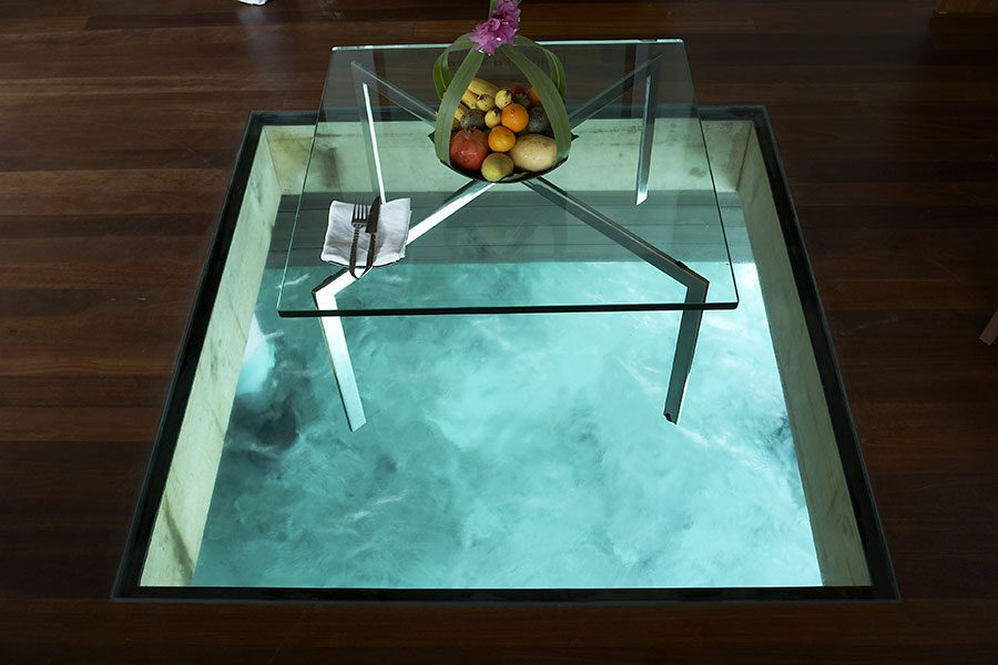 Decorative glass floor panel in a lounge with view to the sea below
